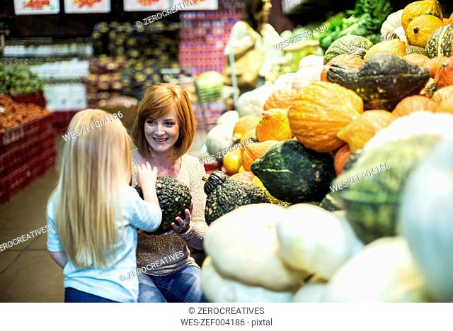 Mother and daughter at supermarket shopping for vegetables