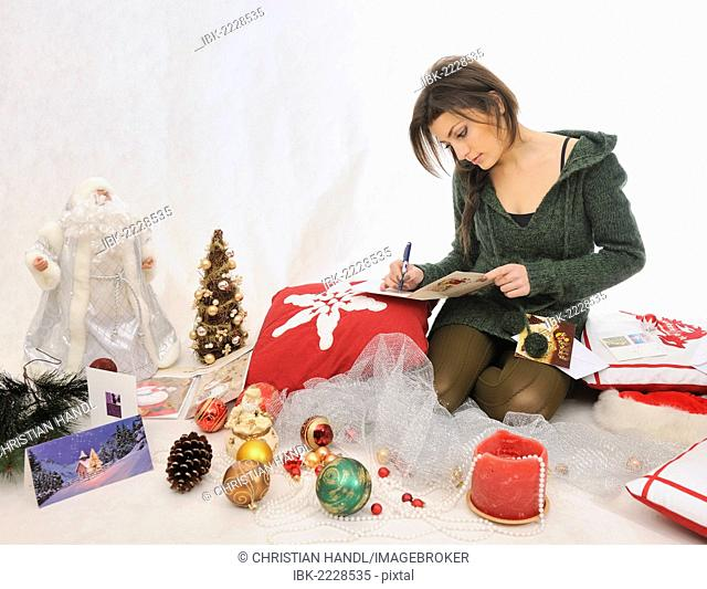 Young woman writing Christmas cards between Christmas decorations