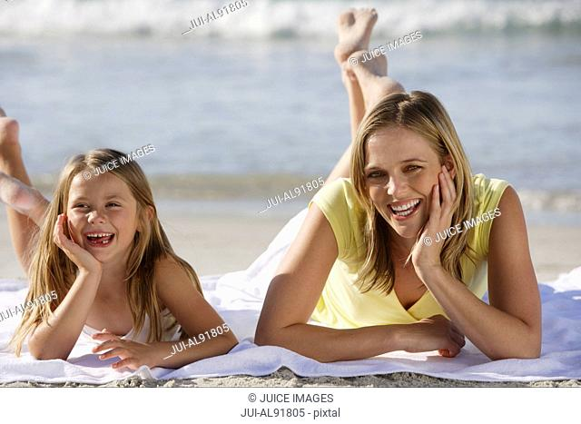 Mother and daughter laying on beach