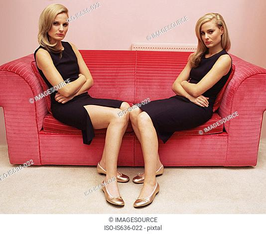 Two women with arms crossed on sofa