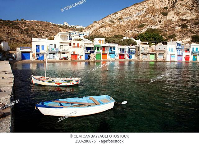 Local people swimming in the sea in front of the traditional fisherman houses with the impressive boat shelters also known as 'Syrmata' in Klima village, Milos