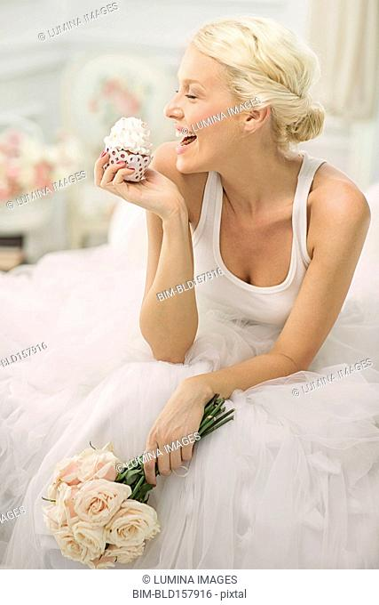 Smiling bride eating cupcake on bed