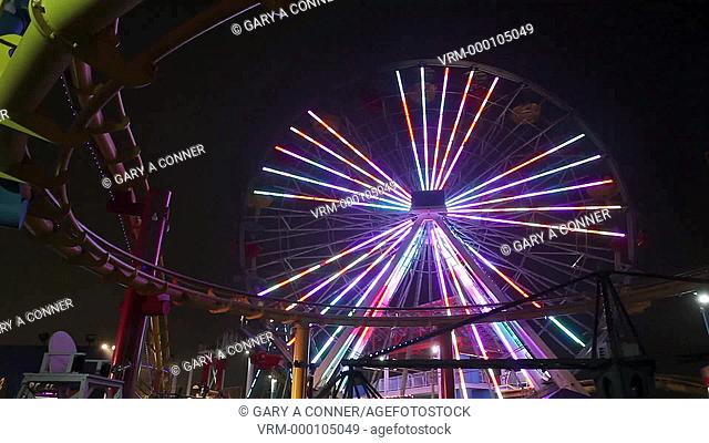 Roller coster and Ferris wheel at night with lights, Santa Monica, CA, USA
