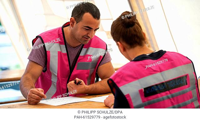 Interpreter Challal and a volunteer write information signs in Arabic, at the provisory refugee shelter, established on the premises of the former barracks in...