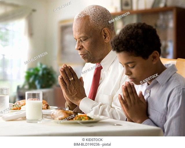 Black grandson and grandfather praying before meal