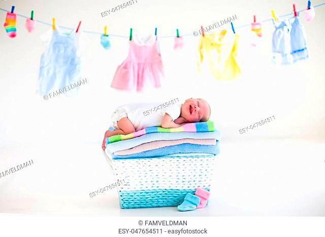Newborn baby on a pile of clean dry towels. New born child after bath in a towel. Family washing clothes. Kids wear hanging on a line