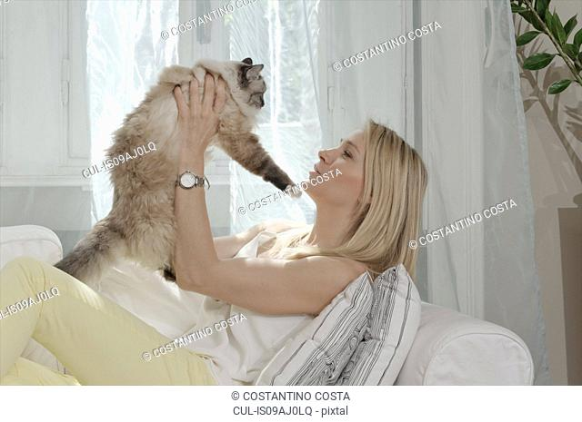 Young woman on sofa holding up cat