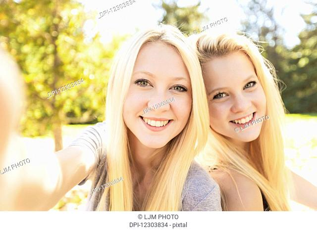 Two sisters having fun outdoors in a city park in autumn taking selfie of themselves; Edmonton, Alberta, Canada