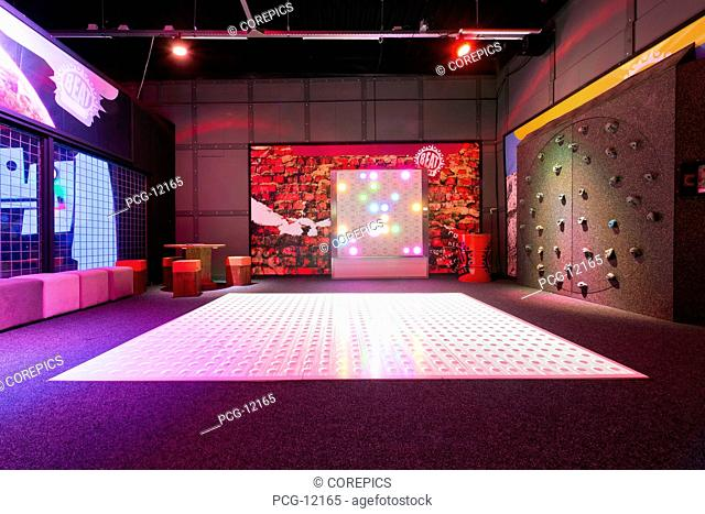 Big electronic gaming mat, with a beamer, projecting the action overhead in an indoor gaming center, Rotating climbing wall and a laser squash game court