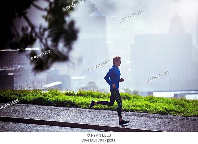 Male runner running on sunny urban sidewalk