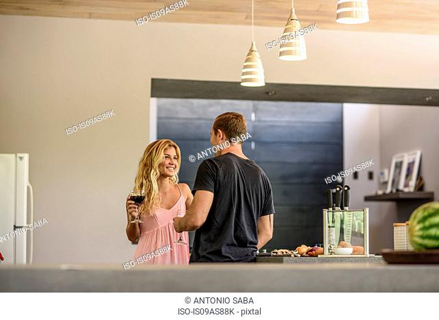 Couple chatting and drinking red wine in kitchen