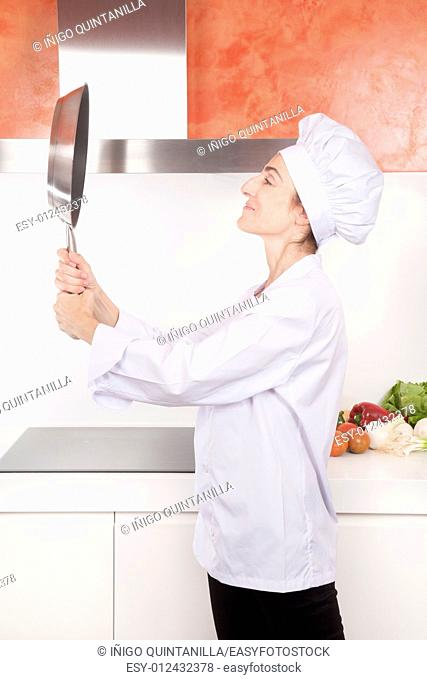 portrait of happy brunette chef woman with professional jacket and hat in white and orange kitchen looking herself at steel blank pan like a mirror
