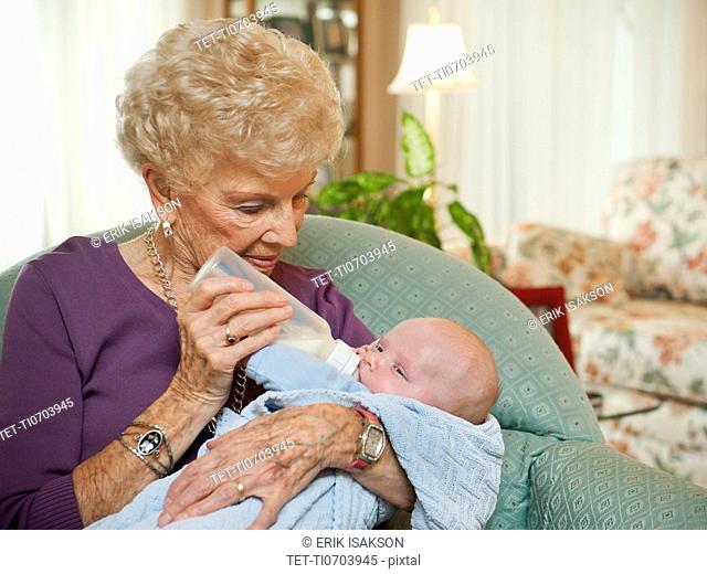 Senior woman giving milk to grandson 2-5 months