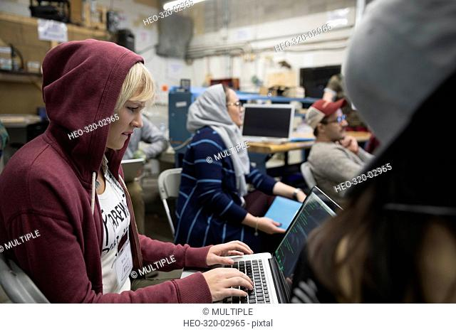 Female hacker wearing hoody working hackathon at laptop in workshop