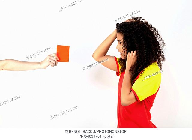 Portrait of a young supporter of the Spain team taking a red card