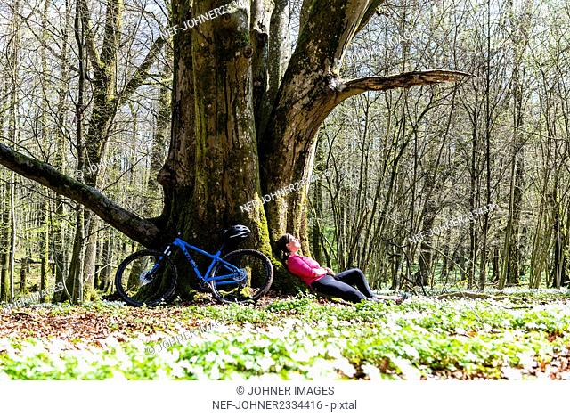 Cyclist resting in forest