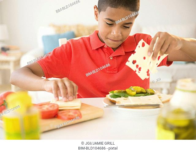 Hispanic boy making sandwich