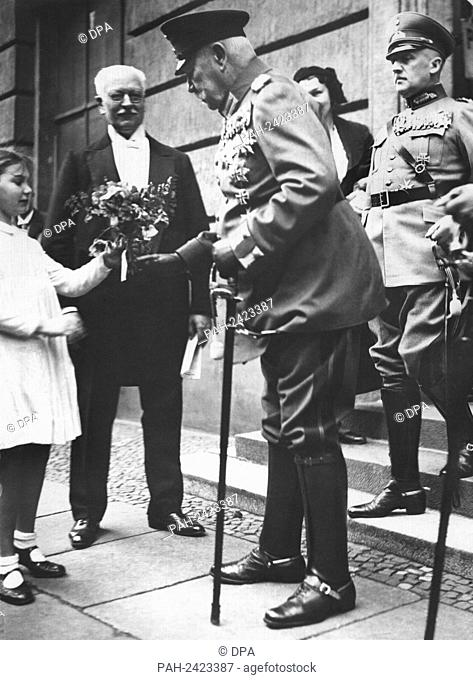 General field marshal and President of the Reich Paul von Hindenburg receives a bunch of flowers from a little girl on the occasion of his 85th birthday on the...