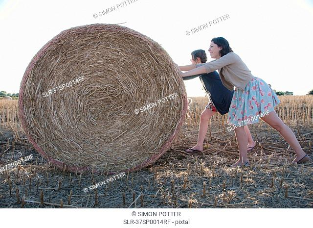 Girls pushing hay bale in field