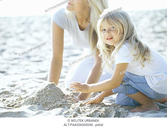 Girl and mother playing in sand