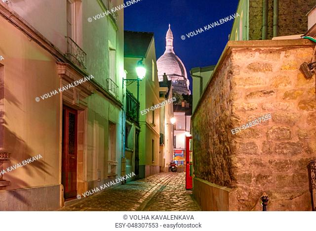 Empty cozy street and the Sacre-Coeur Basilica at night, quarter Montmartre in Paris, France