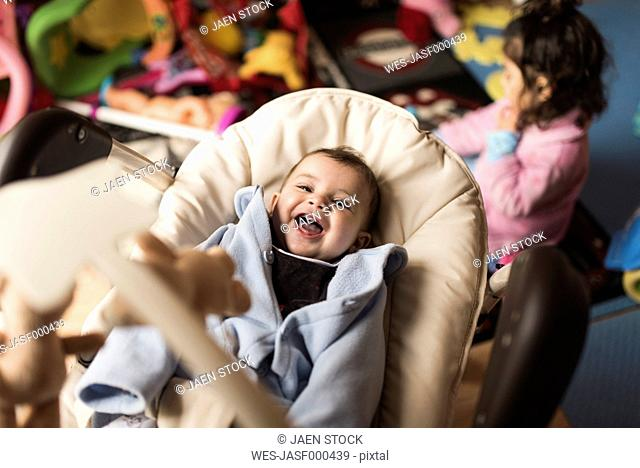 Happy baby boy lying in baby carrier while his little sister playing in the background