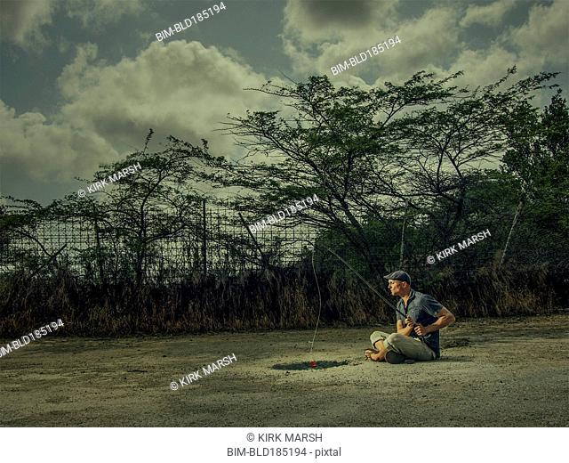Caucasian man fishing in arid puddle