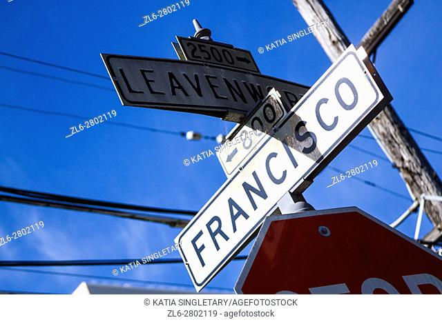 View of white streets signs in San Francisco of an intersection on a blue sky sunny day
