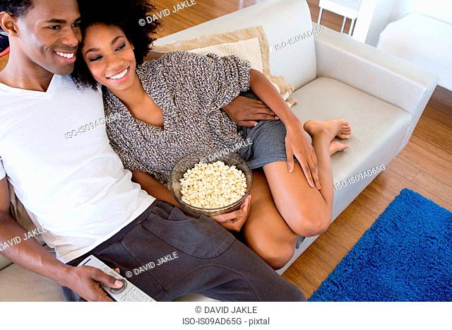 Young couple watching tv with popcorn