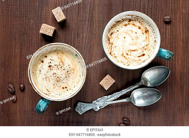 Two cups of coffee and are several pieces of sugar and teaspoons; top view, flat lay