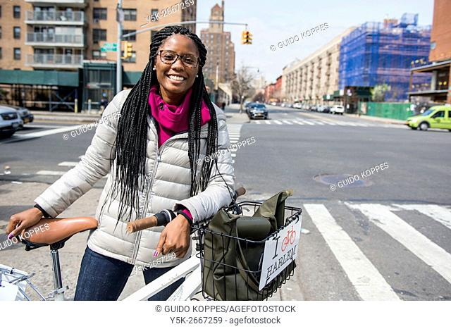 New York City, USA. Attractive African-American woman giving a guided tour by bicycle through Harlem, Manhattan