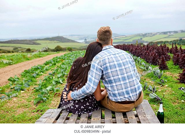 Couple in rural location sitting on pallets looking away