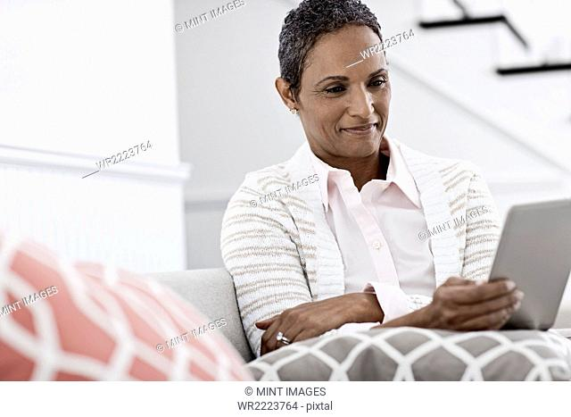 A woman seated using a digital tablet