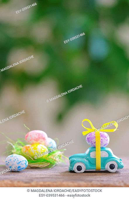 Toy car carrying easter egg in spring time