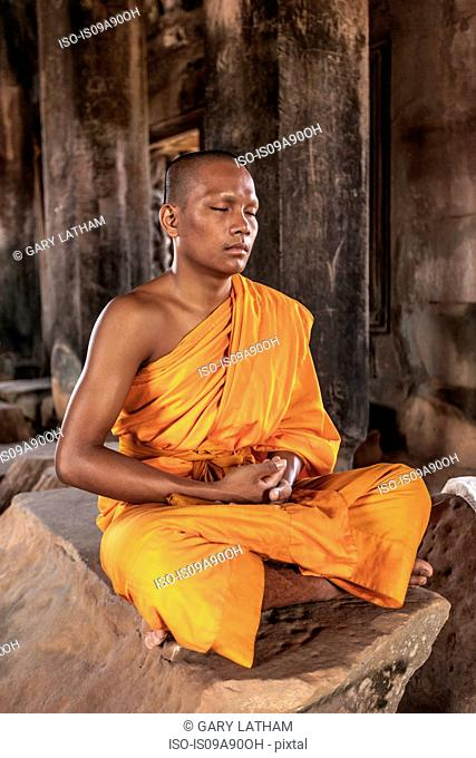Young buddhist monk meditating in temple in Angkor Wat, Siem Reap, Cambodia