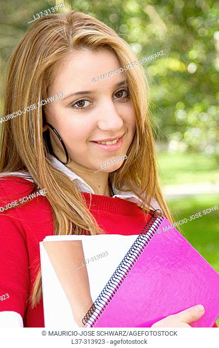 Blonde teenage girl with books in the park
