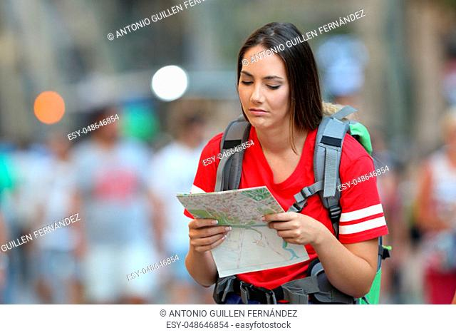 Frustated teen tourist reading a map walking on the street