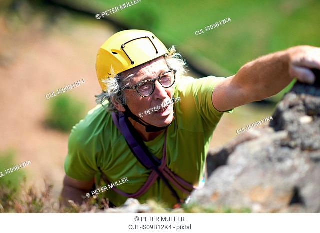 Senior man rock climbing