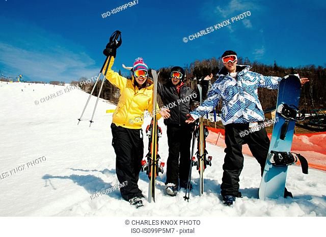 Three friends wearing skiwear with skis