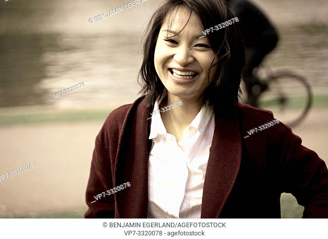 smiling Asian woman outdoors in city, in Frankfurt, Germany