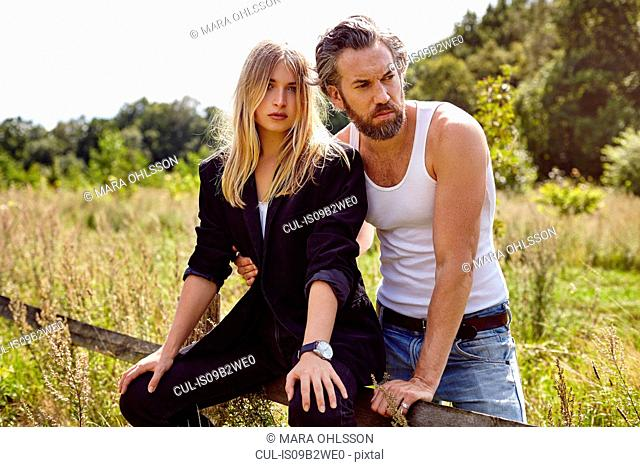 Portrait of couple sitting on rural fence looking sideways