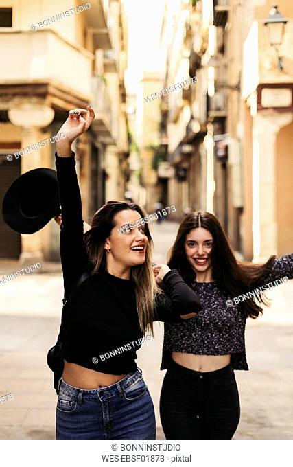 Two happy best friends dancing on the street
