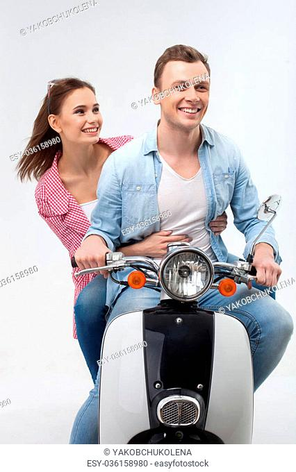That is the real freedom. Cheerful young loving couple is riding motor bike with joy. They are sitting and smiling. The girl is embracing her boyfriend with...