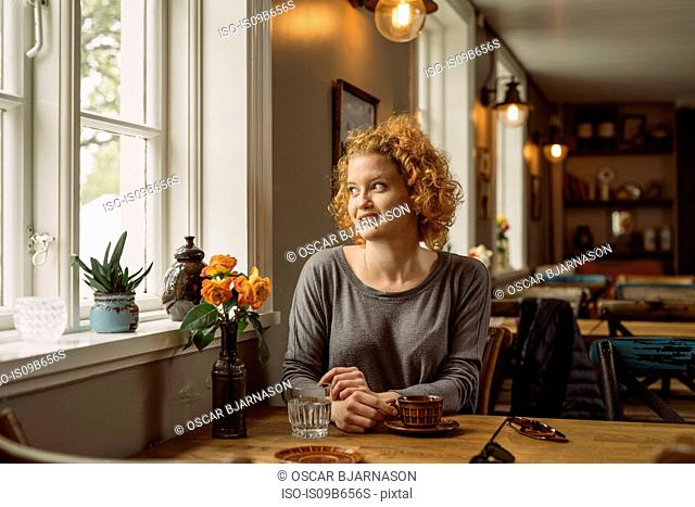 Woman in cafe looking away out of window smiling