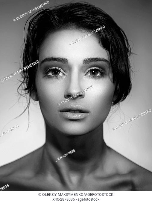 Artistic beauty portrait of a young woman beautiful face with short dark hair, expressive black and white photo
