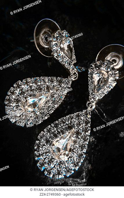 Jewelry fine art photo on a bright glimmering pair of crystal diamante chandelier earrings on black reflecting background. Expensive jewels