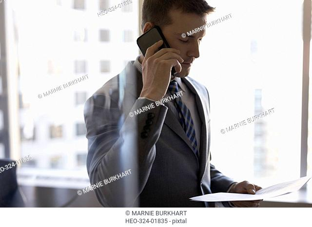 Businessman talking on cell phone and reviewing paperwork