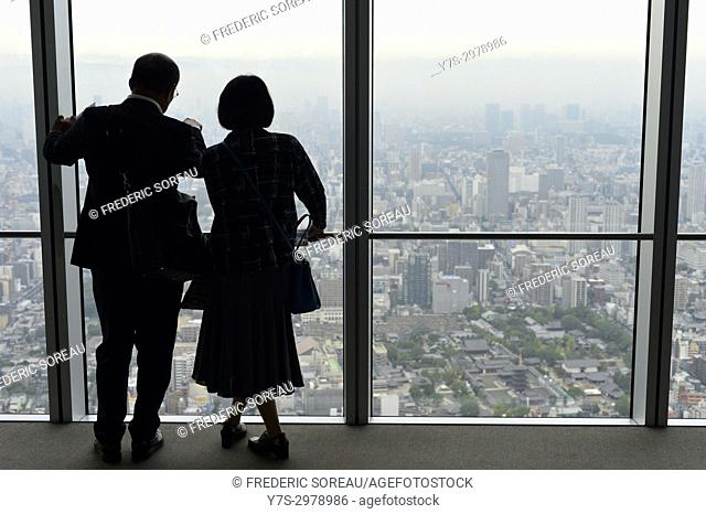 People in silhouette watching Osaka city from the Observation Deck of Abeno Harukas tower, Osaka, Japan, Asia