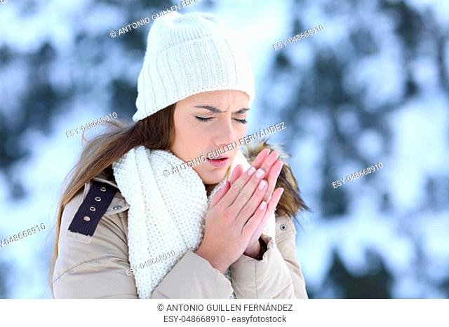 Woman suffering a cold winter outdoors with a snowy mountain in the background