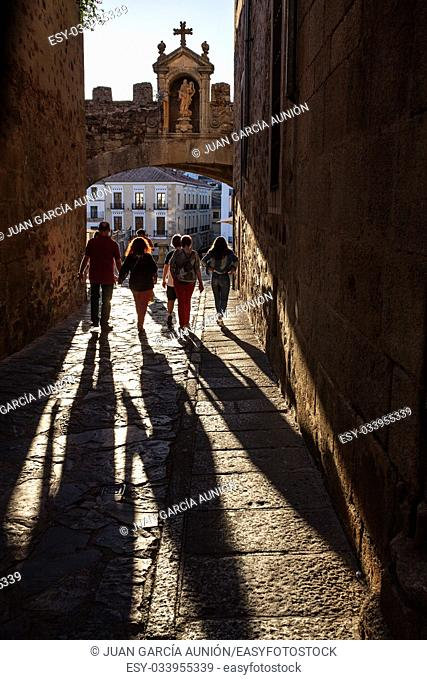 Caceres, Spain - July 1, 2017: Tourists walking under Star Arch or Arco de la Estrella, Caceres. Sunset light